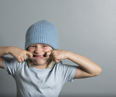 Portrait of boy with fingers in mouth pulling face - ISF02392