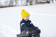 Young boy sitting on sledge, in snow covered landscape - ISF02419