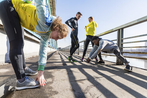 Friends doing stretching exercise on bridge in the city - WPEF00312