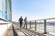 Friends running on a bridge in the city - WPEF00315