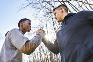 Two sportive young men shaking hands outdoors - WPEF00324