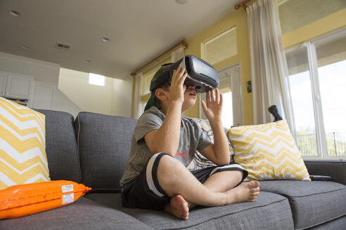 Young boy sitting cross legged on sofa, wearing virtual reality headset - ISF02521