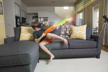 Young boy on sofa, wearing virtual reality headset, firing laser guns, digital composite - ISF02524
