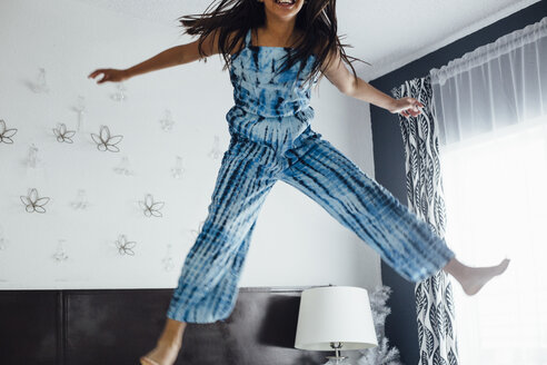 Girl jumping in mid air smiling - ISF02539