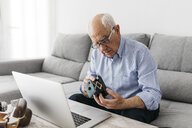 Senior man using laptop and holding his old photo camera - JRFF01665