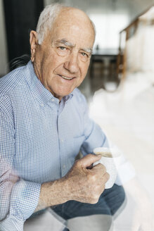 Senior man having a coffee while relaxing at home, looking at camera through a glass - JRFF01674