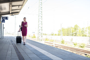 Mature businesswoman with smartphone and suitcase walking at platform - DIGF04470