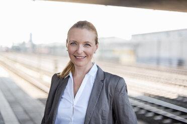 Portrait of smiling businesswoman at platform - DIGF04482