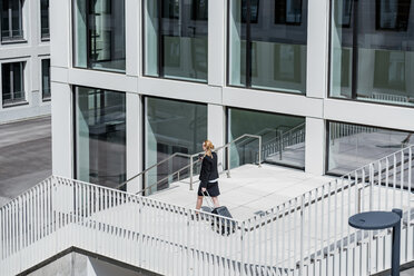Businesswoman with suitcase and coffee to go walking in front of office building - DIGF04488