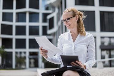 Portrait of smiling businesswoman with documents and tablet sitting in front of office building - DIGF04494