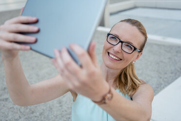Portrait of smiling woman wearing glasses taking selfie with tablet - DIGF04497