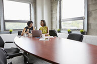 Two women sitting at meeting room table, using laptop - ISF02603