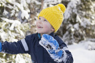 Boy in yellow knit hat looking up in snow covered forest - ISF03081