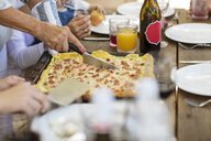 Woman cutting up pizza at lunch table - ISF03114