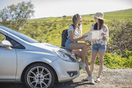 Two young women beside car, looking at map - ISF03195