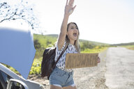 Young woman standing beside car, holding hitch-hiking sign saying 'anywhere', gesturing with hand - ISF03210