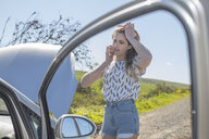Young woman beside broken down car, using smartphone - ISF03213