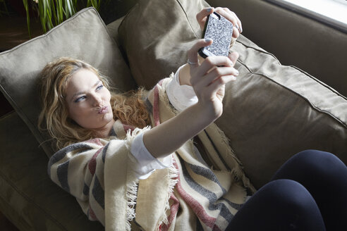 Woman taking selfie on sofa - ISF03279