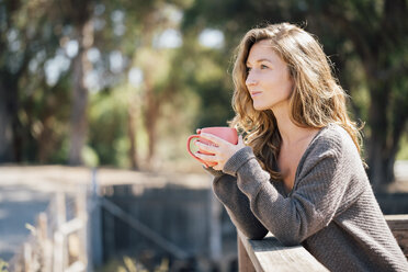 Young woman, outdoors, leaning on fence, holding coffee cup - ISF03306
