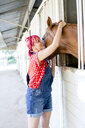 Woman with pink hair petting horse at stable door - ISF03333
