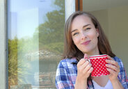 Portrait of young woman holding coffee mug by patio door - ISF03438