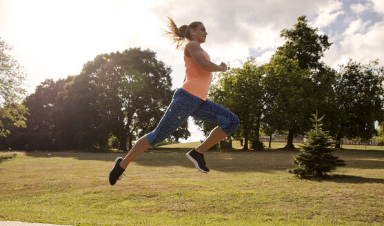 Young woman training in park, leaping mid air - ISF03480