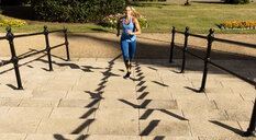Young female runner running up park stairway - ISF03486