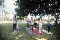 Schoolgirls practicing yoga mountain pose on school sports field - ISF03567