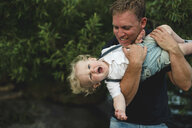 Mature man holding up toddler son - ISF03636