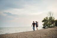 Pregnant couple strolling along beach with male toddler son, Lake Ontario, Canada - ISF03642
