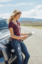 Woman leaning against car looking at map - ISF03669