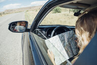 View over shoulder of woman sitting in car looking at map - ISF03672