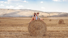 Friends sitting back to back on top of hay bale looking at camera smiling - ISF03699