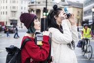 Two young stylish women taking photographs on street, London, UK - ISF03726