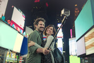 Couple taking selfie with selfie stick in Times Square, New York, United States, North America - ISF03747