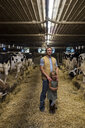 Portrait of farmer and daughter in cow shed - ISF03765