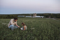 Father and daughter on farm, tending to crops - ISF03777