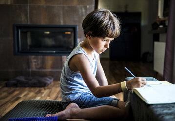 Boy kneeling on floor drawing in workbook - ISF03789