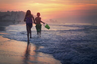 Siblings paddling in sea at sunset, North Myrtle Beach, South Carolina, United States - ISF03792