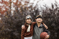 Portrait of girl and twin brother wearing basketball player and pilot costumes for halloween in park - ISF03813