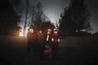 Portrait of boy and girls posed in halloween costumes in garden at dusk - ISF03816