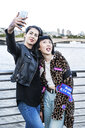 Two young stylish women taking smartphone selfie on millennium footbridge, London, UK - ISF03825