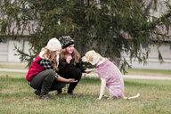 Girl and her sister crouching to hold dog's paw in garden - ISF03855