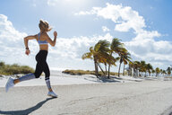Young female runner running at beach - ISF03903