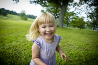 Portrait of blond haired girl running in rural field - ISF03963