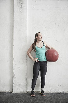 Woman carrying fitness ball in cross training gym - ISF04071