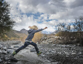 Boy leaping over rocks on riverbed - ISF04203