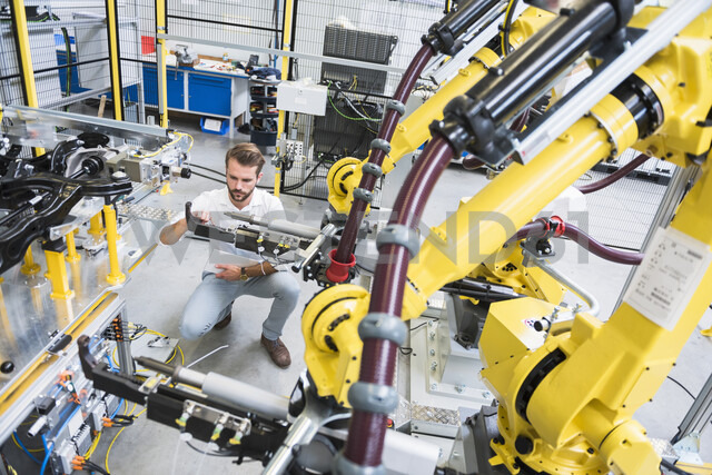 Young male engineer testing machinery in engineering factory - ISF04395 - Daniel Ingold/Westend61