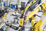 Young male engineer testing machinery in engineering factory - ISF04395