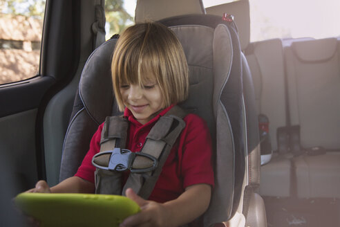 Girl in car safety seat looking at digital tablet - ISF04458